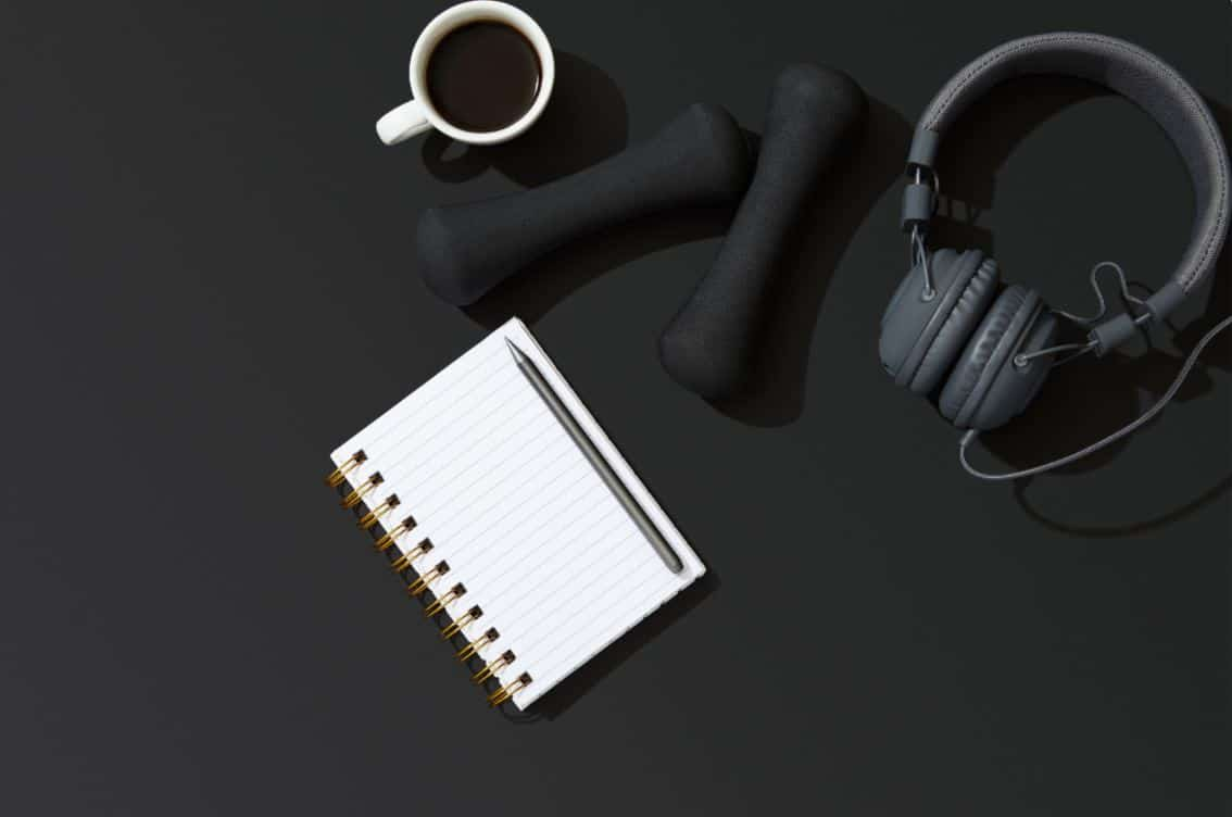 Gym equipment on floor with notepad and a coffee